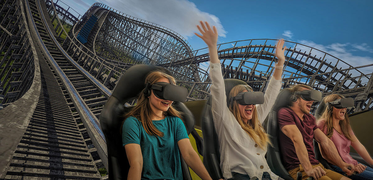 Row of laughing and smiling friends experiencing VR InMotion coaster.